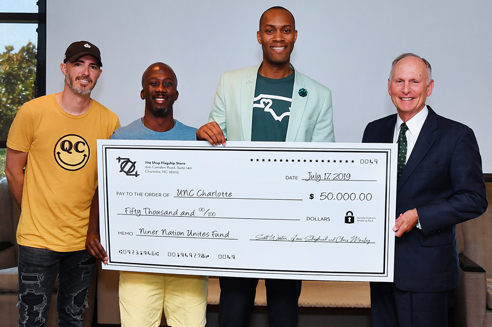 Scott Wooten, Jerri Shephard '13 and Chris Moxley '03, presented a $50,000 check for the Niner Nation Unites Fund to Chancellor Dubois