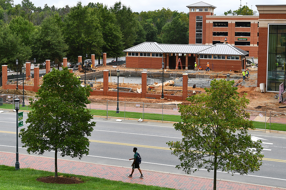 UNC Charlotte student walks by URC construction