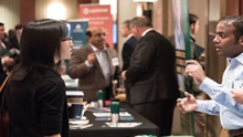 Attendees from a previous conference interact with exhibitors